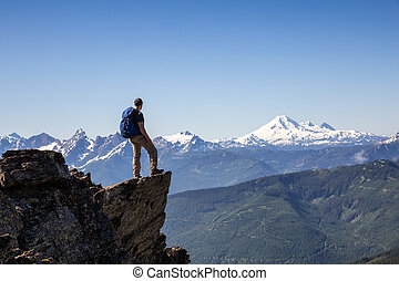 Man on the Edge of a Cliff looking at Canadian Landscape