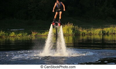 Man on the flying board on the river, water jet spray. Man on the flying board flies over the lake water. Fly board rider. new water sport called fly board.