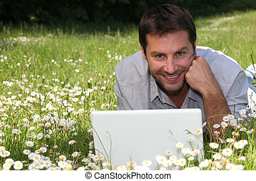 man on the grass with laptop