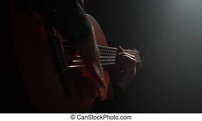 Man on the guitar plays the Latin rhythm. Close up
