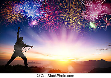 man on the mountain and watching sunrise and fireworks