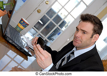businessman at his dining room table with PDA