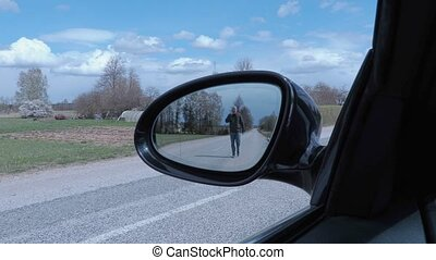 Man on the road in car mirror