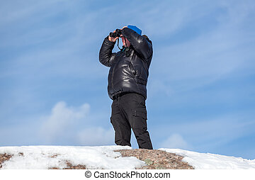 Man on the rock looking at binoculars on blue sky background