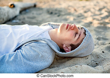 Man on the Sand - Young Man sleep on the Sand closeup...
