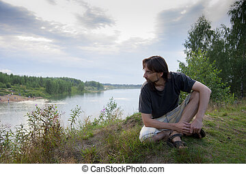 man on the shore of lake
