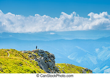 Man on the top on a green mountain