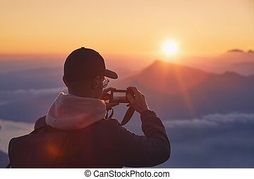 Man on top of mountain photographing sunrise