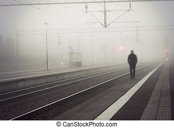 Man on train platform - silhouette of man in blurred motion...