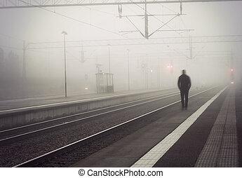 Man on train platform - silhouette of man in blurred motion...