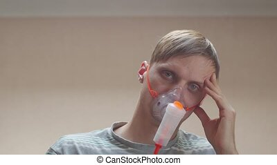 Man on treatment is napping portrait closeup in oxygen mask unshaven messy male interior