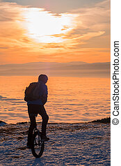 Man on unicycle riding on mountain over fog to sunset - Man...