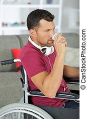 man on wheelchair drinking from a cup
