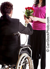 Man on wheelchair giving a flowers