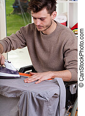 Man on wheelchair ironing shirt