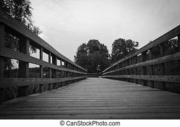 man on wooden bridge black and white