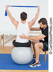 Man on yoga ball working with a physical therapist - Young...
