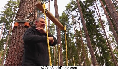 Man on zip line in forest