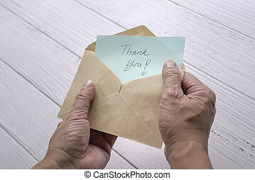 Man open and look at thank you card or note inside a brown envelope