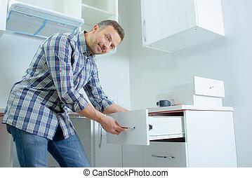 man opening a kitchen drawer