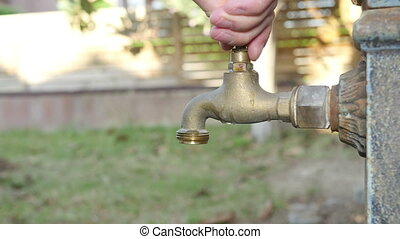 Man opening an Old Fashioned Tap - Old faucet dripping. Iron...