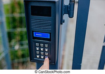 Man opening automatic property gate with security code on outdoor intercom