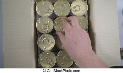 Man opening cardboard box with canned food