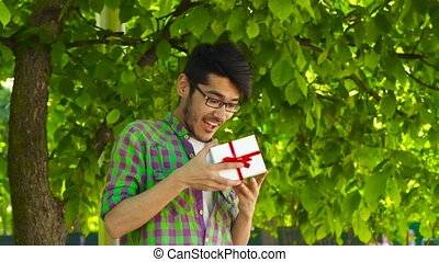 Man opening gift in park - Happy asian guy smiling and...