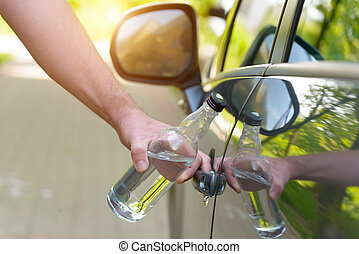 Man opening his car while holding a bottle of alcohol