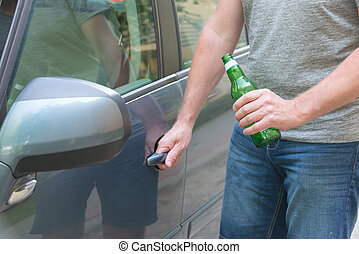 Man opening his car while holding a bottle of beer