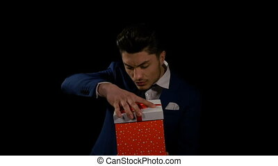 Man opening surprise gift box with a look of joyful...