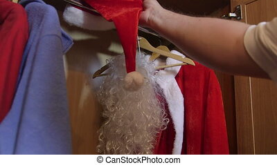 Man opening the closet door and pulling out Santa Claus suit...