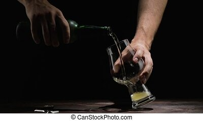 male hand pours beer into a glass on the table - man opens a...