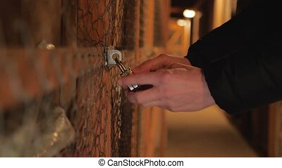man opens a combination lock on a storage room in the attic