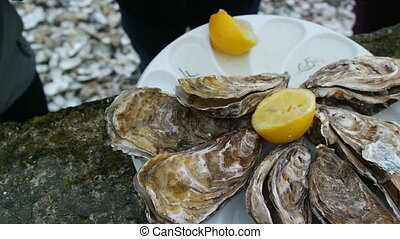 Man opens an oyster and waters it with lemon juice