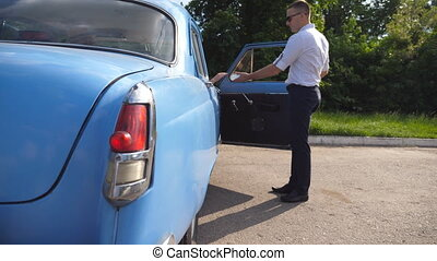 Man opens and holds the door of old car for the beautiful...