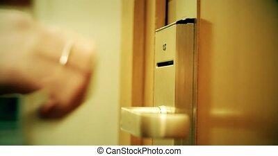 Man opens hotel room door with card