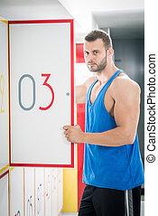Man opens locker door in gym
