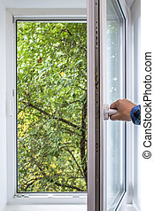 man opens pvc window