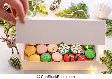 man opens the lid of the box with his hand. Variety of sweet macaroons in white box. The branches of spruce on bokeh background. Modern european French cuisine. Christmas theme, Merry Christmas card.