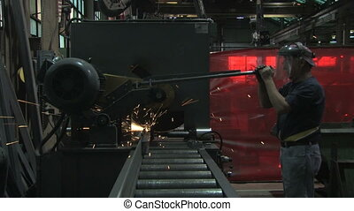 Man Operates Machine 2 - A factory worker cuts a large metal...