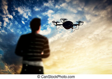 Man operating a drone at sunset.