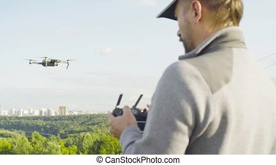 Man operating a drone quadrocopter with camera - Rear view...