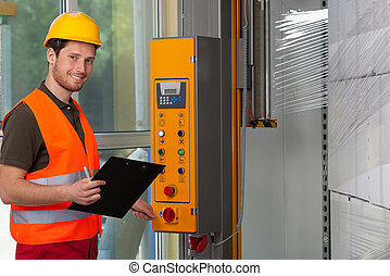 Man operating a wrapping machine - Man in protective vest ...