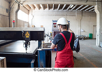 man operating control panel in industrial hall