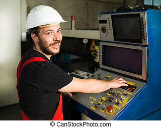 man operating control panel in industrial setting