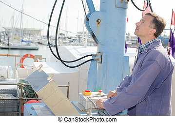 Man operating crane on quayside