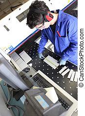 Man operating cutting machine in workshop