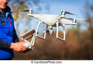 Man operating drone flying by remote control in the park