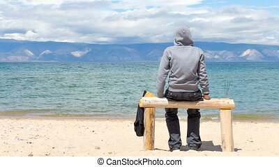 Man or woman is sitting in a hoodie on the beach. Back view....